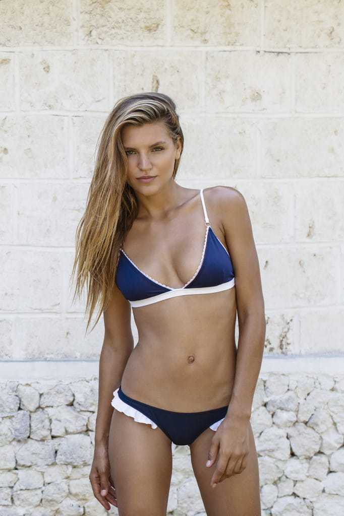 Balistarz-model-Anastasia-Bluemoloko-standing-in-front-of-wall-wearing-blue-white-swim-suit