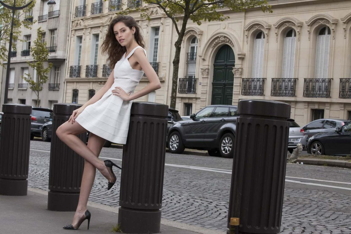 Balistarz-model-Anni-Barros-leaning-against-a-metal-miniture-pillar-in-a-white-dress-with-a-beautitul-scenery
