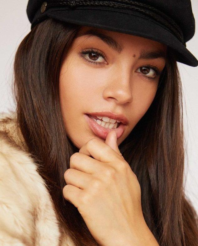 Balistarz-model-Arielle-Panta-headshot-profile-joyful-thumb-on-lip-black-hat
