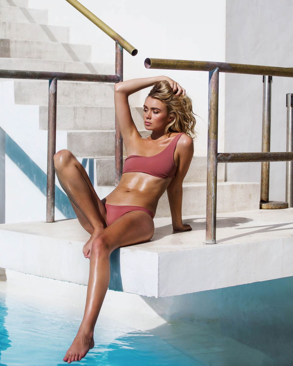 Balistarz-mode-Claudia-Thompson-sitting-on-a-ledge-over-a-pool-looking-stunning-as-gold