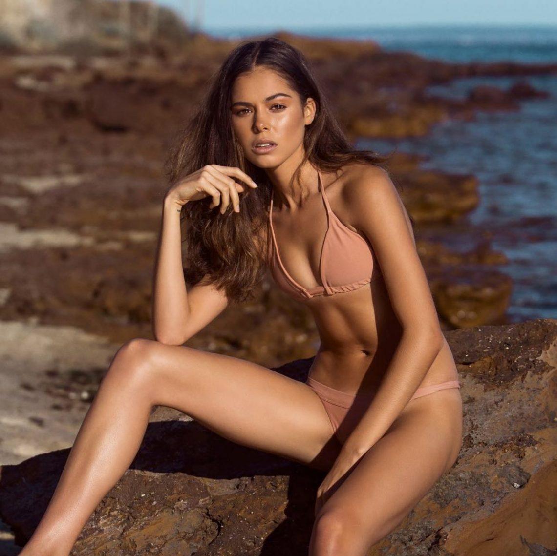 Balistarz-model-Elissa-Burns-sitting-on-beach-rock-in-her-sexy-calm-colour-bikini