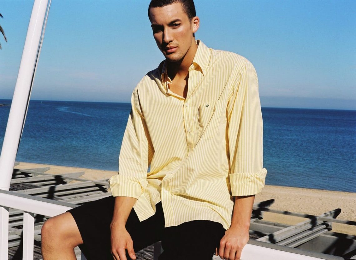 Balistarz-model-Emile-Steenveld-casual-shot-near-the-beach-wearing-yellow-shirts-over-blue-ocean-background