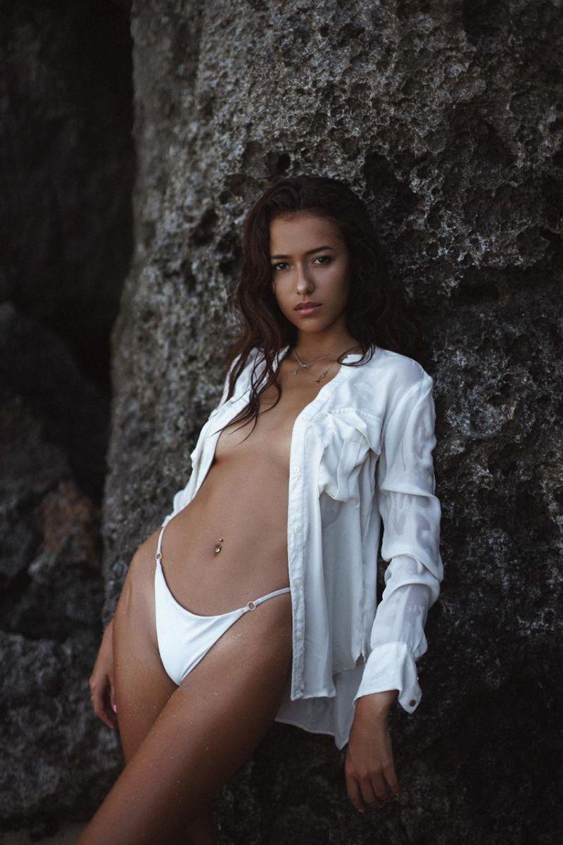 Balistarz-model-Jasine-Giles-portrait-shoot-with-a-jacket-leaning-on-rocks