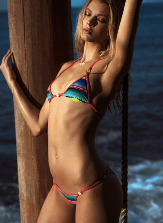 Balistarz-model-Jesse-Wave-portrait-shoot-in-a-rainbow-bikini-holding-onto-a-wooden-pole-near-the-ocean