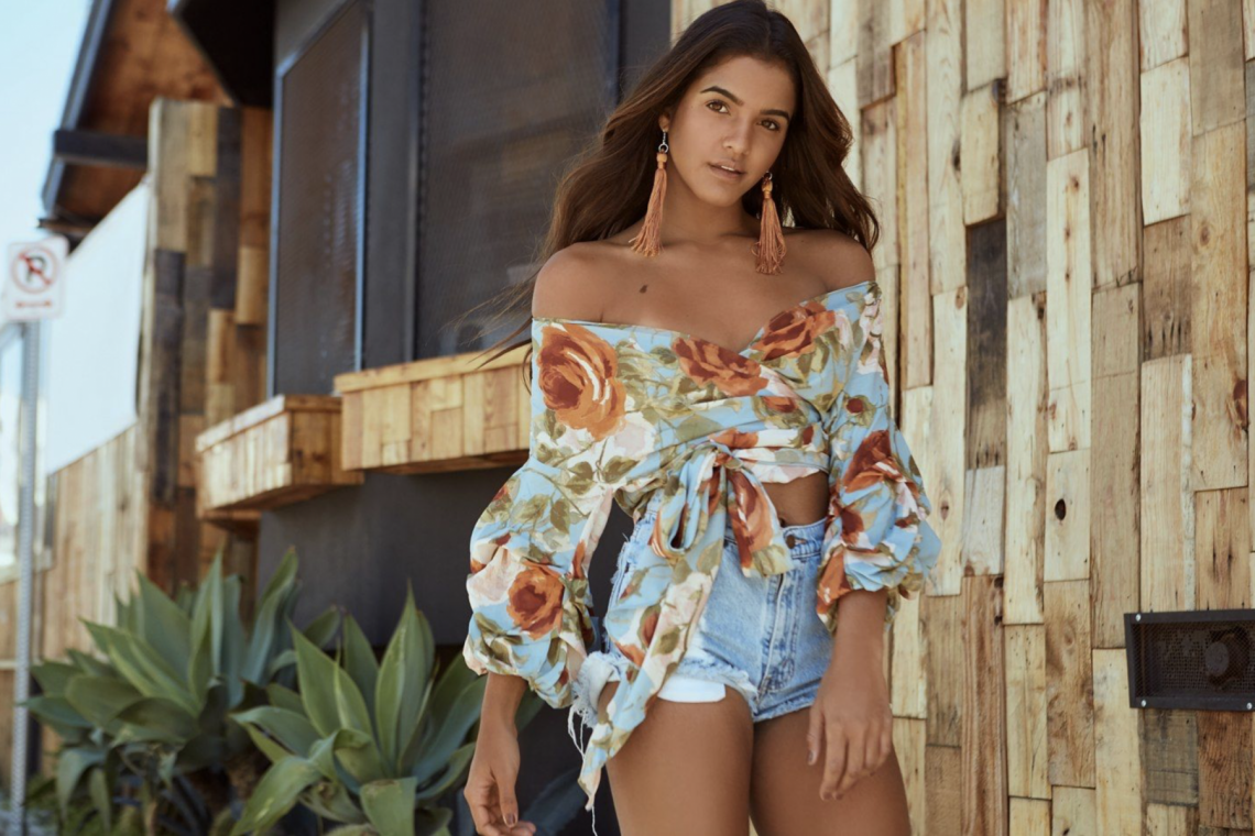 Balistarz-model-Julia-Muniz-landscape-shoot-with-a-flower-top-and-shorts-with-a-wooden-house