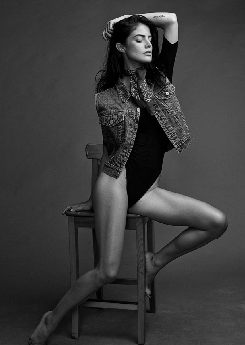 Balistarz-model-June-Peers-black-and-white-portrait-shoot-stretching-on-a-chair-with-a-jacket-with-a-tie