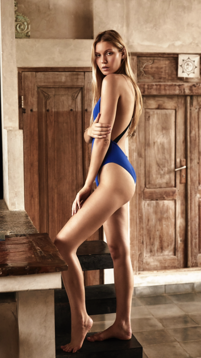 Balistarz-model-Laura-Ziedone-posing-stands-in-her-blue-swim-suit-side-shoot