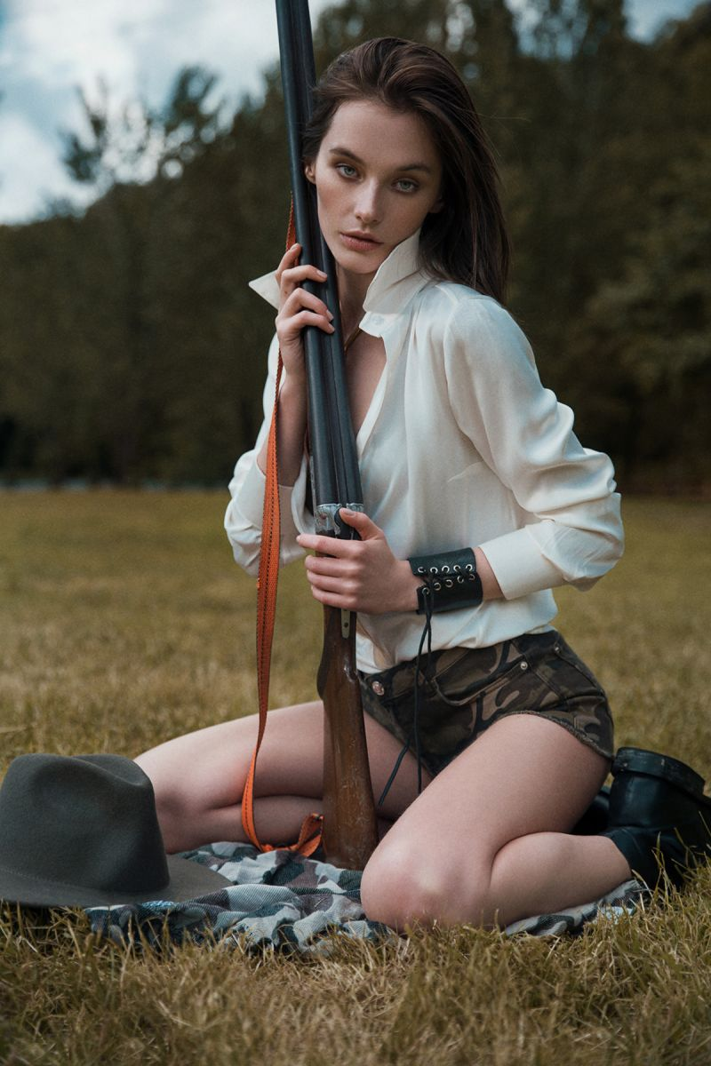 Balistarz-model-Lisa-Ababkova-portrait-shoot-in-camo-shorts-and-a-white-button-up-holding-a-gun-sitting-on-the-grass