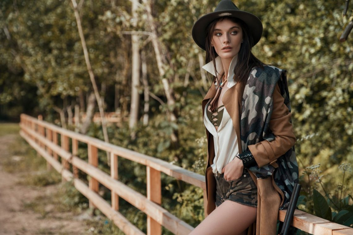 Balistarz-model-Lisa-Ababkova-landscape-shoot-with-camo-shorts-and-brown-coat-sittng-on-wooden-fence