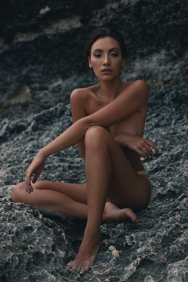 Balistarz-model-Lizette-Croes-sitting-on-a-rock-with-sand-and-a-necklace