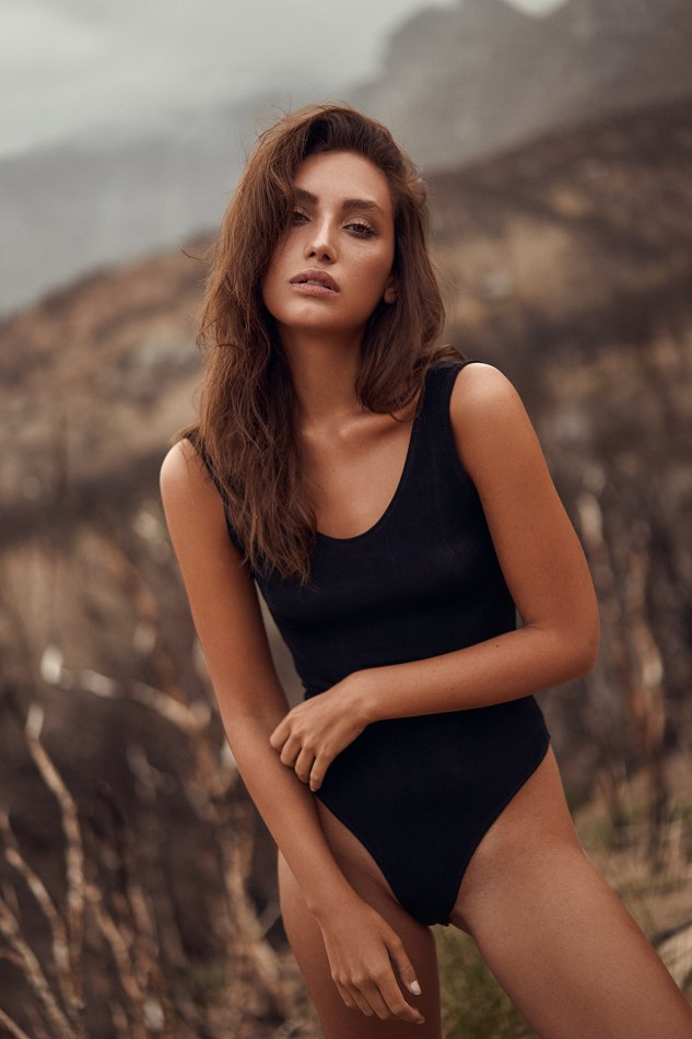 Balistarz-model-Lizette-Croes-in-black-swimwear-in-a-brown-field-on-a-cloudy-day-looking-seductive