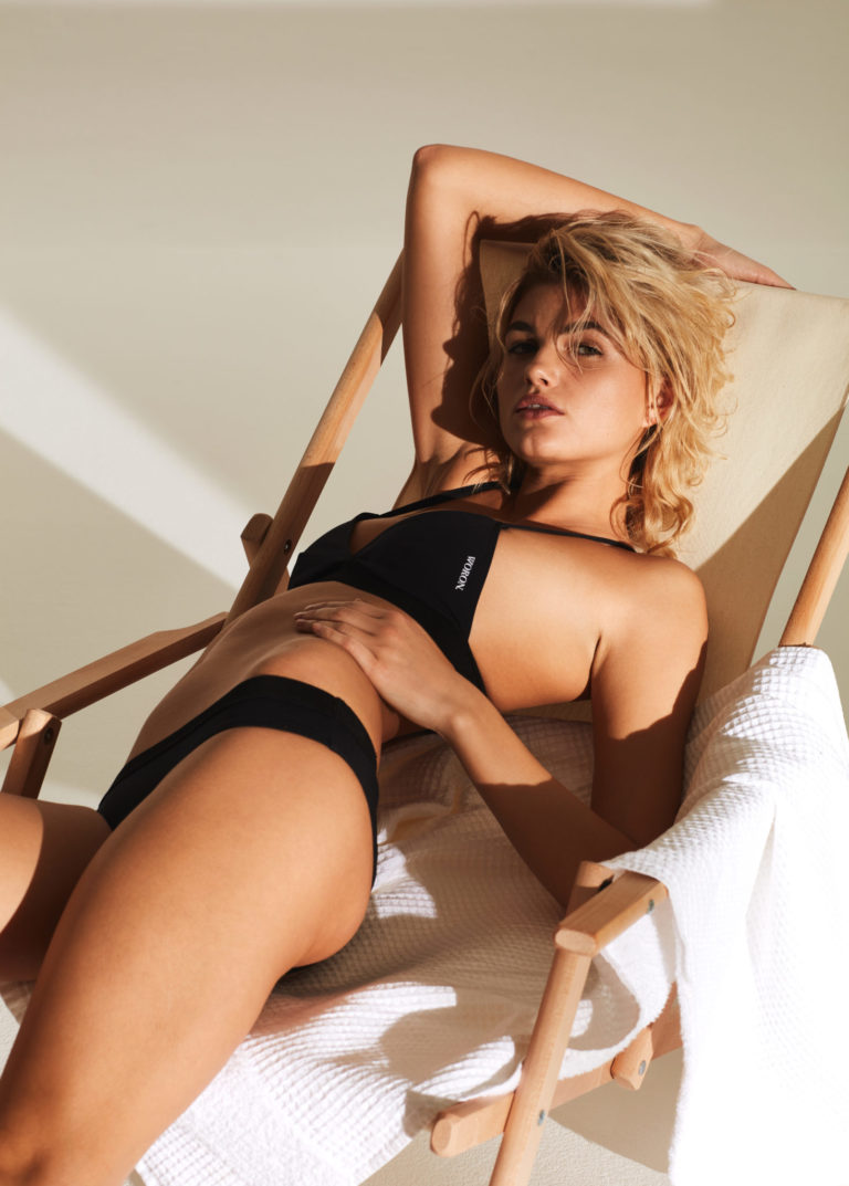 Balistarz-model-Louise-Mikkelsen-shot-for-woron-swim-wear-laying-on-the-sun-bed-in-black-swim-suit