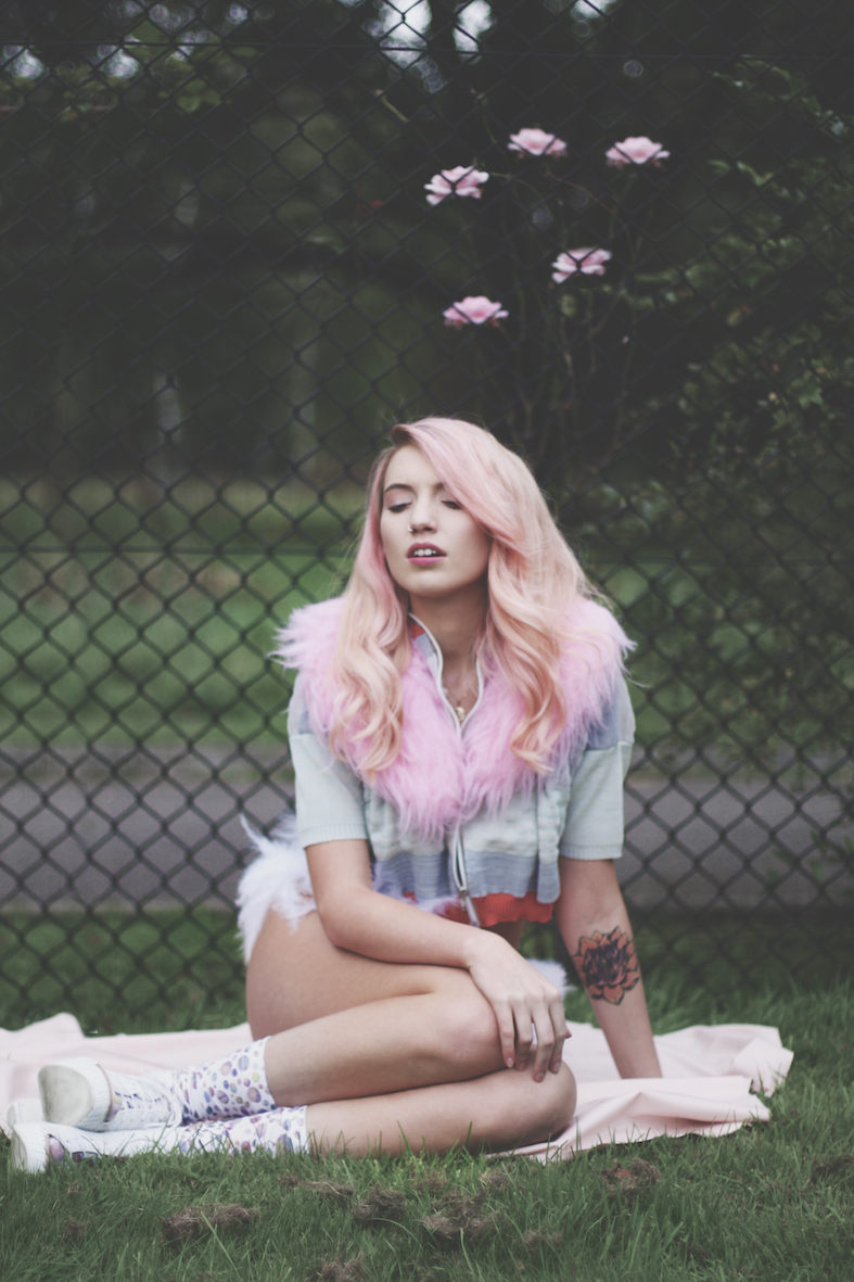 Balistarz-model-Maddie-Quinn-wearing-a-pink-jacket-as-the-pink-fur-acts-like-cotton-candy-as-she-rests-at-the-park-with-beautiful-pink-flowers