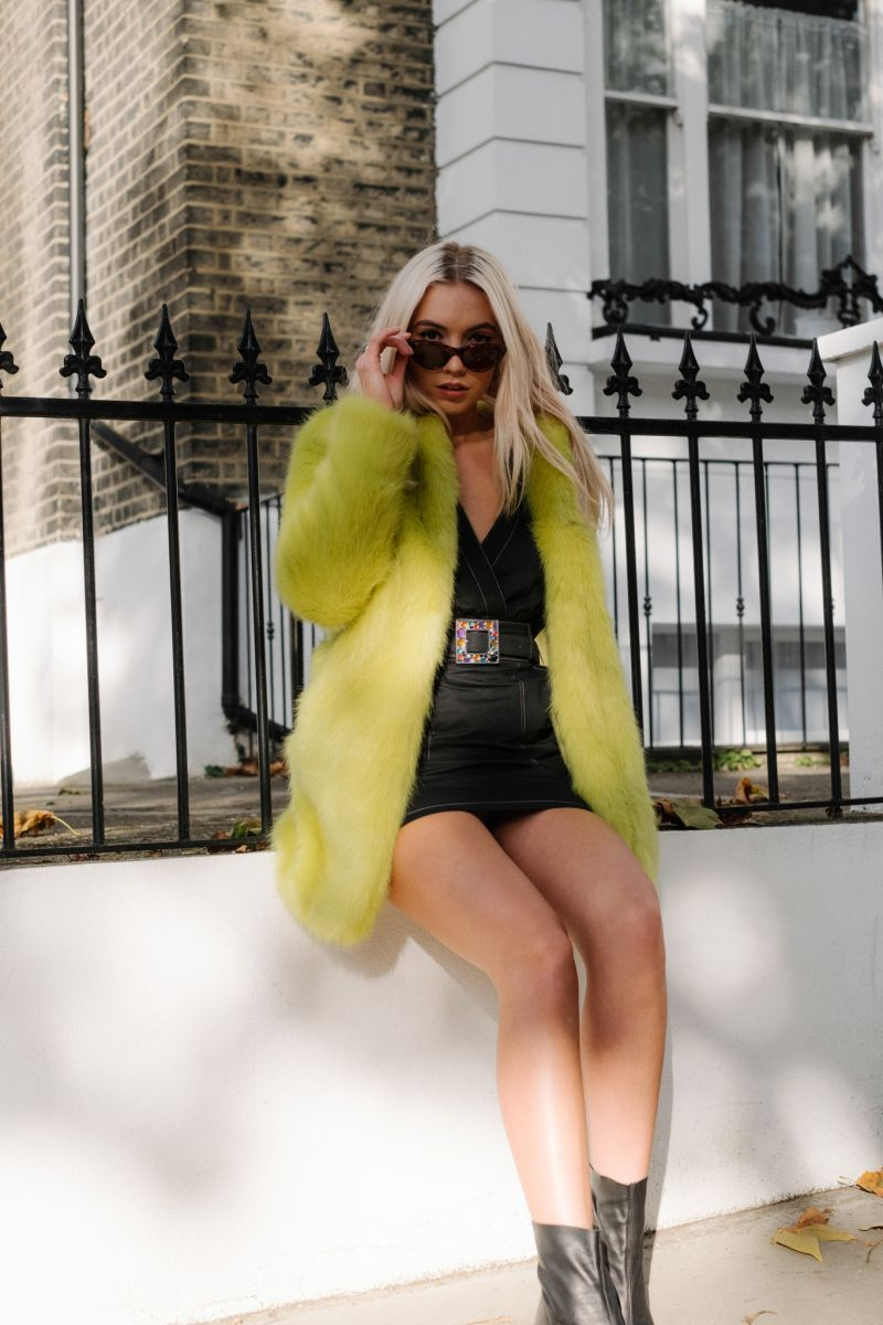 Balistarz-model-Maddie-Quinn-in-a-stylish-green-coat-with-a-stylish-black-dress-pulling-her-glasses-down