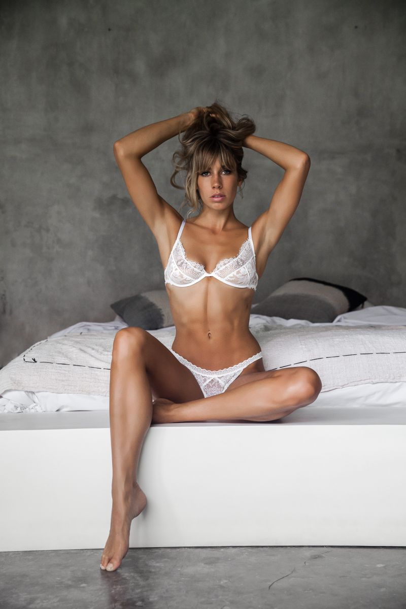 Balistarz-model-Madeline-Relph-sitting-at-the-side-of-the-bed-wearing-white-lingerie-by-le-cocon-doux