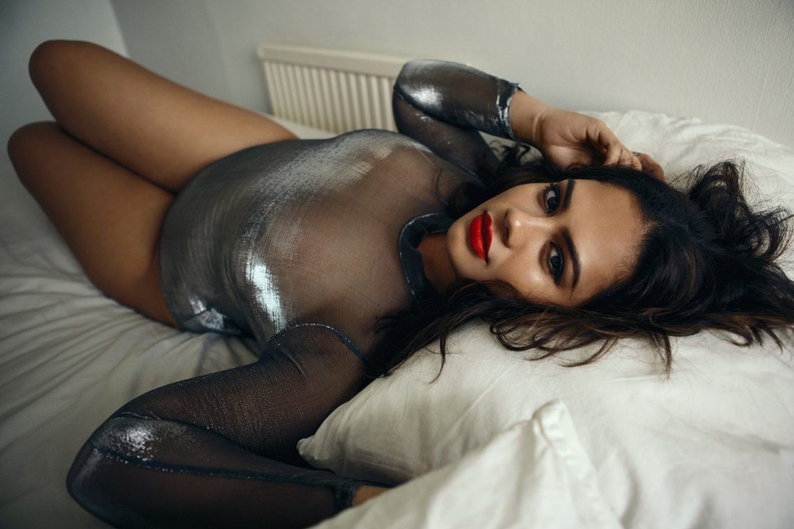 Balistarz-model-Mahalia-portrait-shoot-with-grey-tight-long-sleeve-laying-on-bed