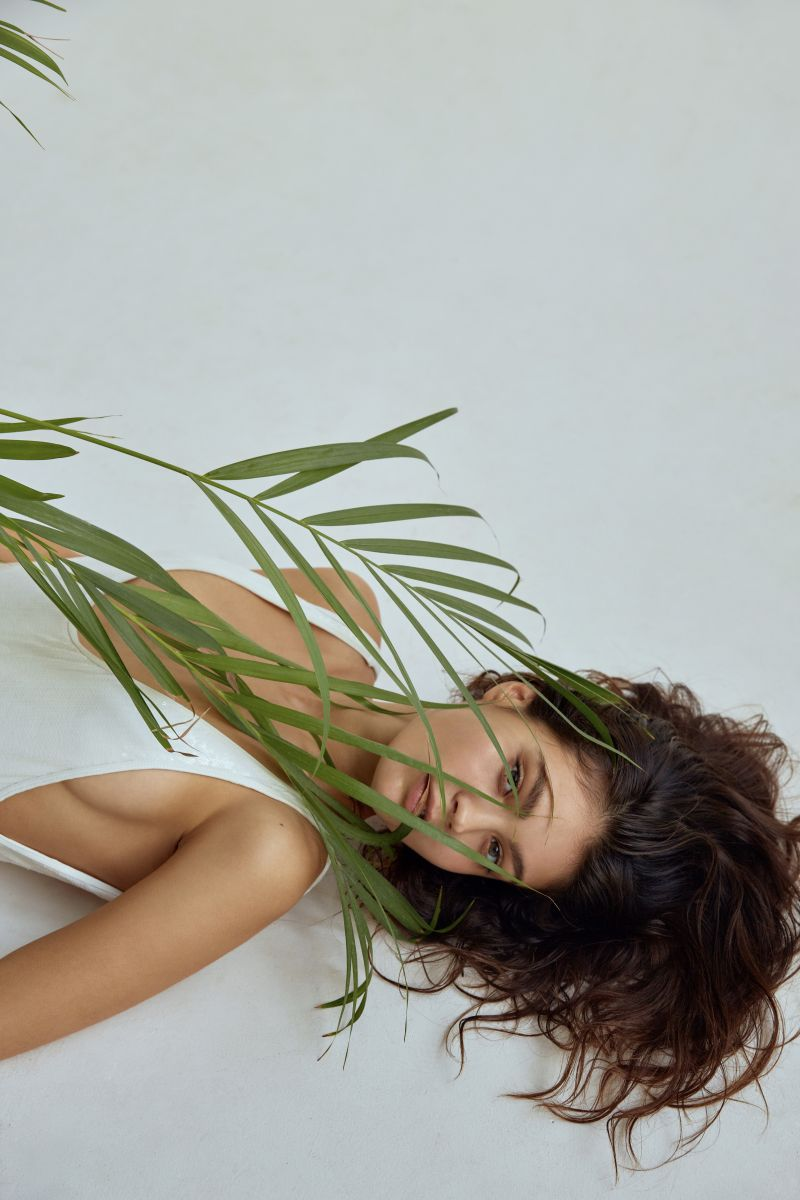 Balistarz-Marina-Yarosh-portrait-shoot-laying-down-in-a-white-tank-top-with-a-plant