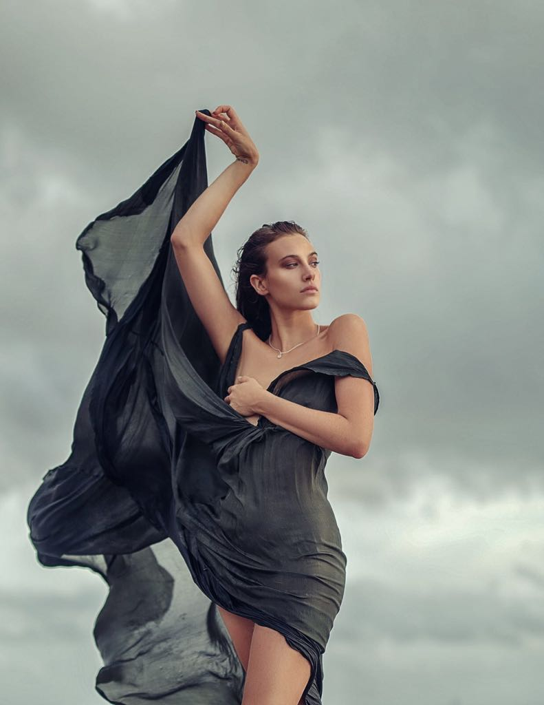 Balistarz-model-Meg-Lindsay-holding-a-long-black-dress-up-into-the-stormy-dark-clouds