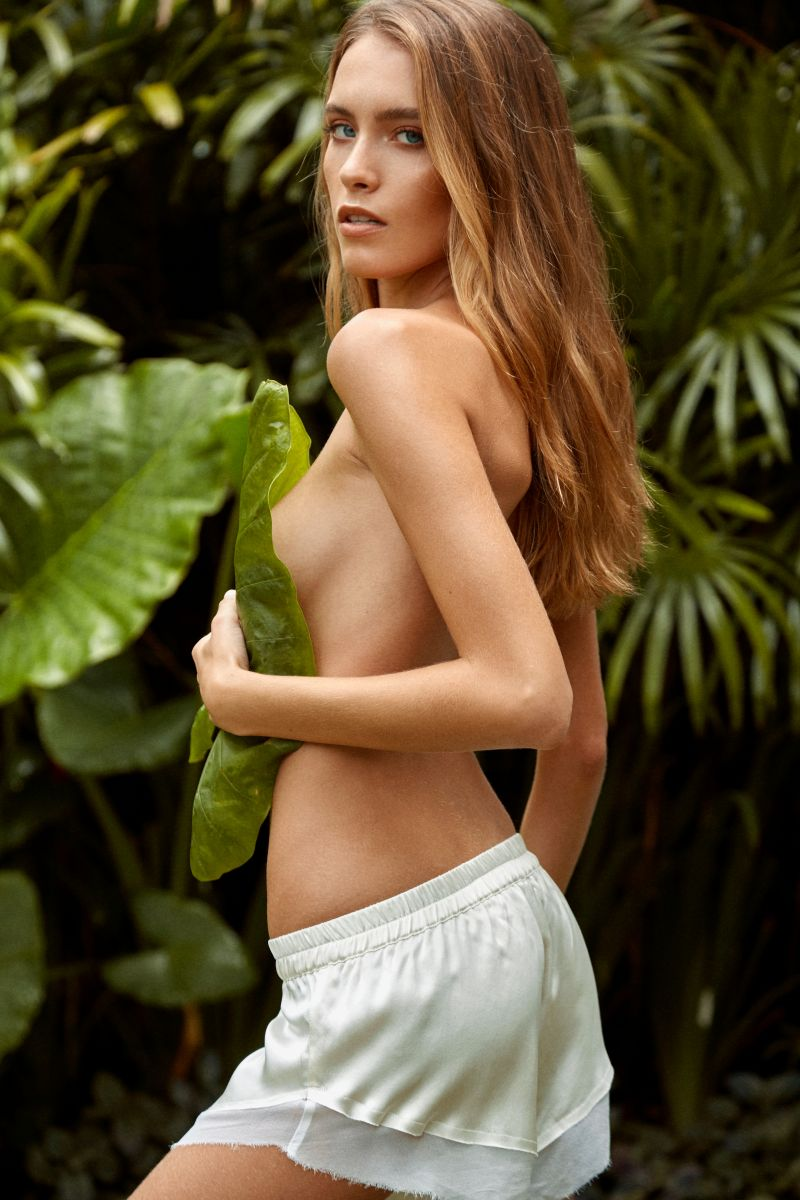 Balistarz-model-Nastya-Beresneva-wearing-white-shorts-in-a-garden-with-a-leaf-covering-her