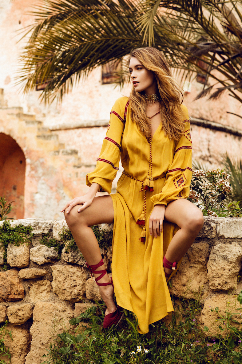 Balistarz-model-Nastya-Beresneva-outside-sitting-on-a-wall-with-a-red-and-yellow-dress-looking-quite-happy