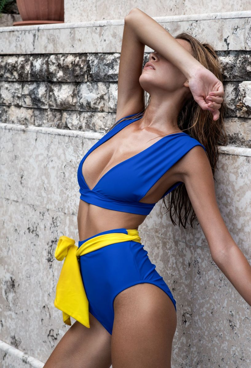 Balistarz-model-Nastya-Beresneva-in-blue-swimwear-with-a=yellow-tie-protecting-her-eyes-from-the-light