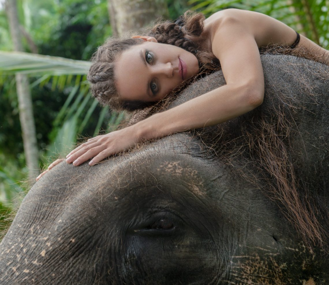 Balistarz-model-Natalia-Brhel-landscape-shoot-laying-on-top-of-a-elephant