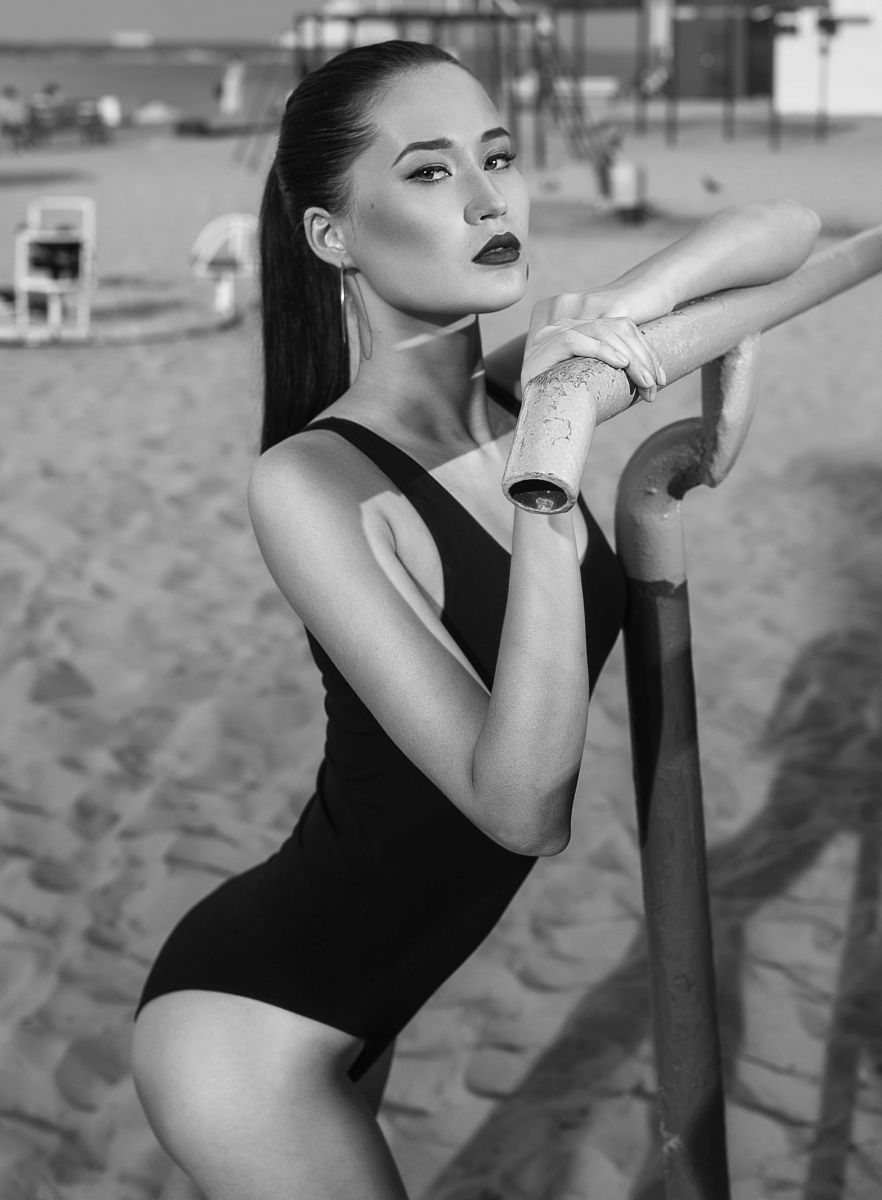 Balistarz-model-Olga-Portnova-black-and-white-portrait-shoot-holding-on-a-rail-in-a-black-swimsuit