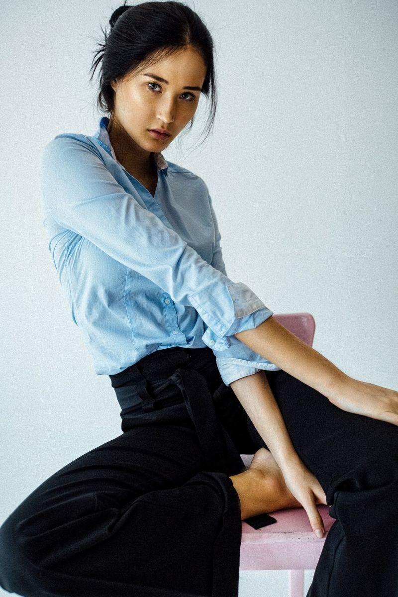 Balistarz-model-Olga-Portnova-portrait-shoot-sitting-on-a-pink-chair-in-a-blue-shirt-and-black-pants