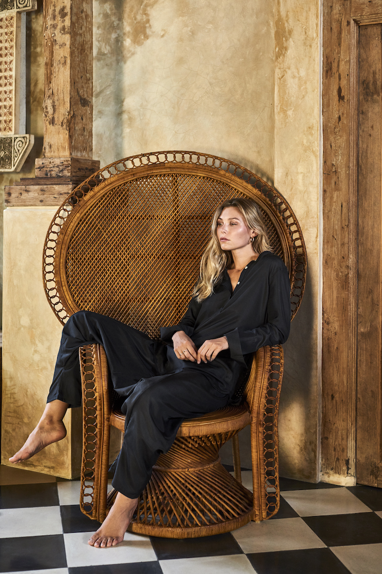 Balistarz-model-Olya-Nechiporenko-sitting-on-a-huge-lounge-chair-wearing-black-casual-travel-wear-outfit-by-sassind
