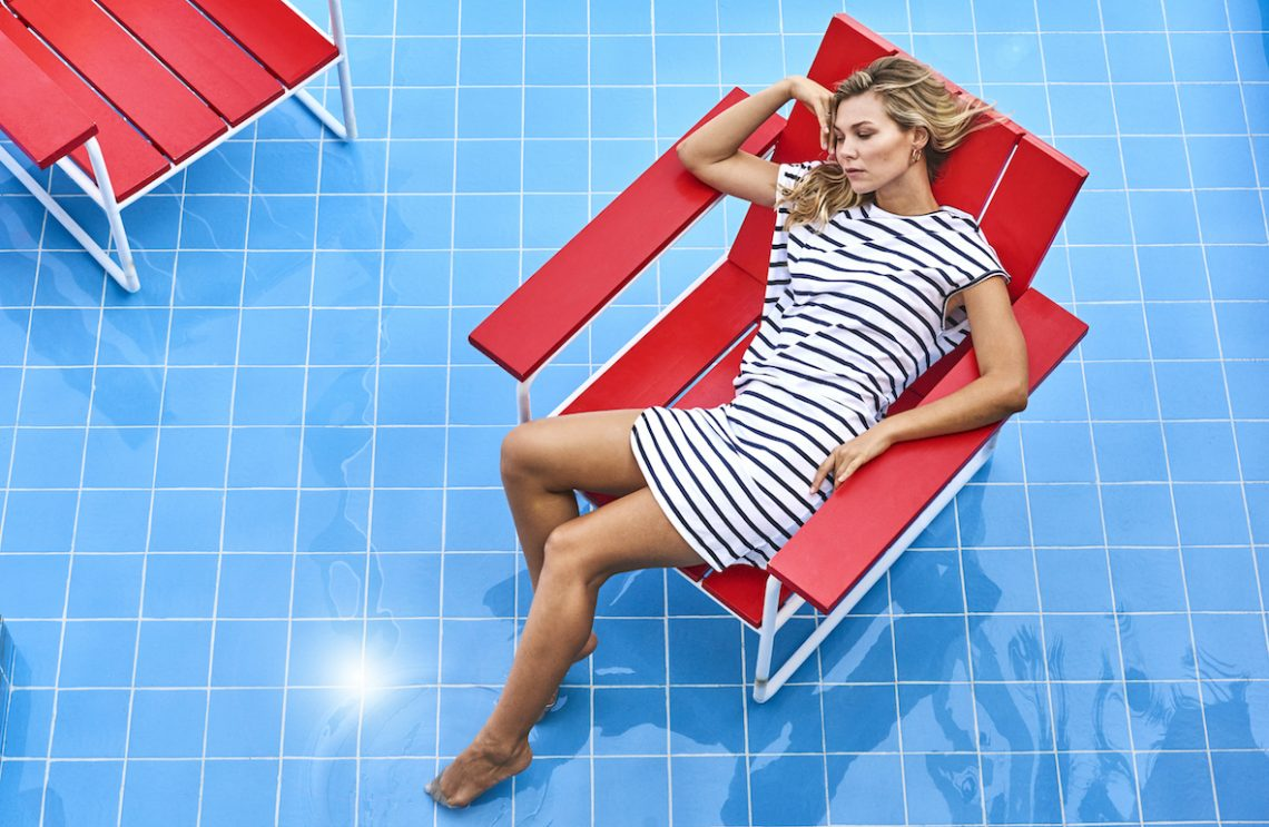 Balistarz-model-Olya-Nechiporenko-sitting-at-a-red-chair-on-the-blue-floor-wearing-casual-dress-travel-wear-by-sassind