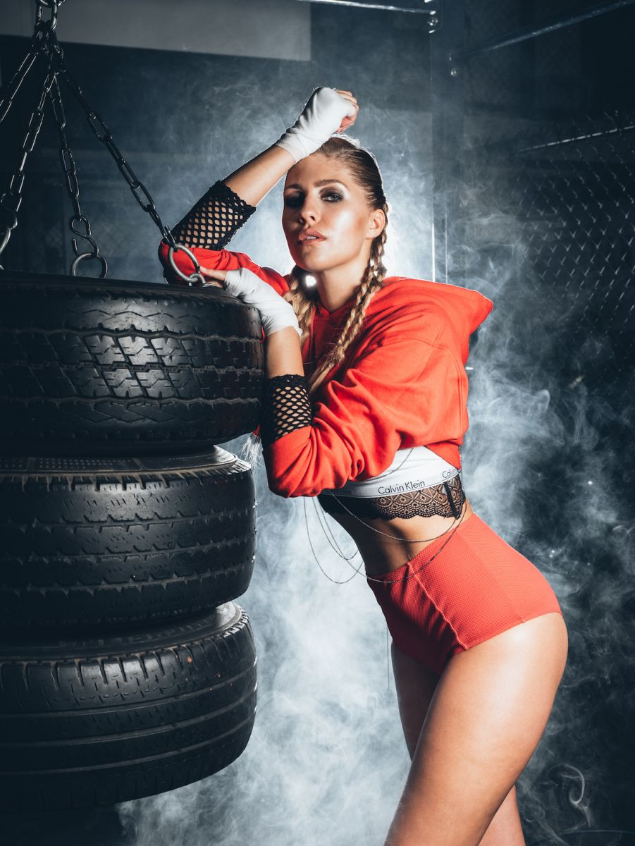 Balistarz-model-Rachel-Bowler-portrait-shoot-in-casual-orange-clothing-resitng-on-a-tire
