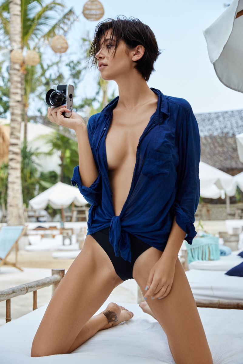 Balistarz-model-Raluca-Cojocaru-wearing-blue-pool-suit-holding-camera-at-hand