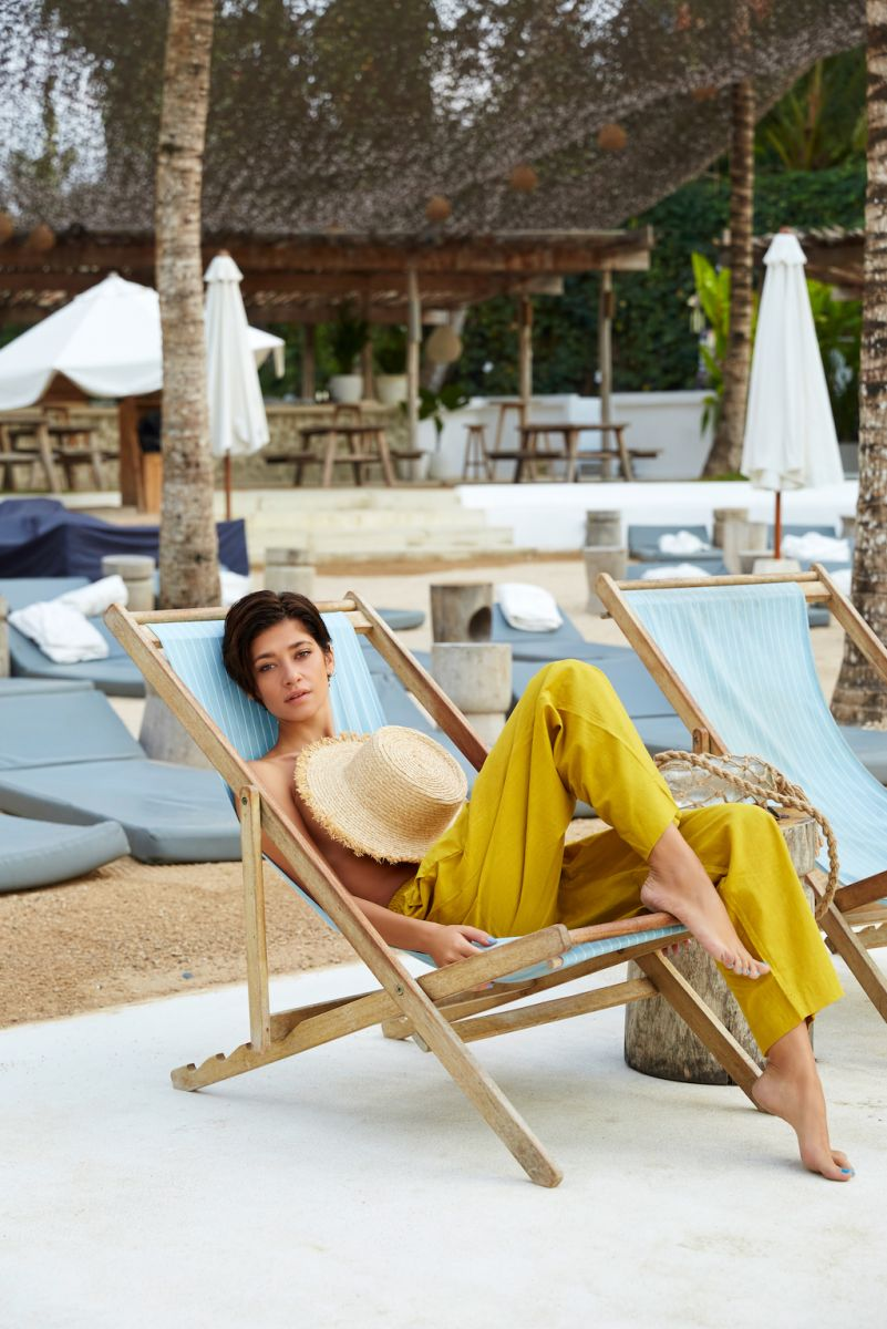 Balistarz-model-Raluca-Cojocaru-sitting-on-beach-couch-in-yellow-trousers