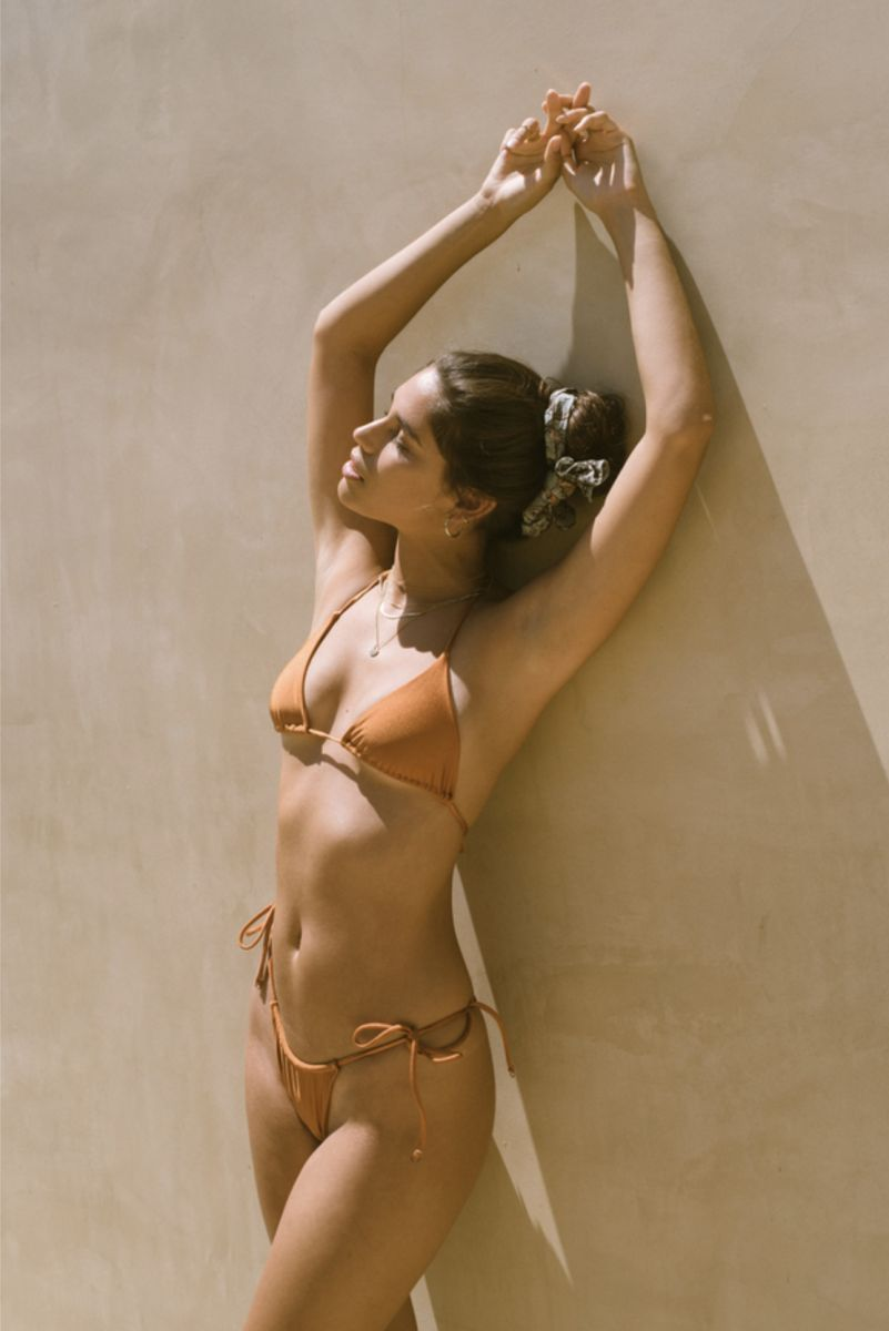 Balistarz-model-Samantha-Garza-portrait-shoot-in-a-orange-bikini-with-accessories-against-a-wall