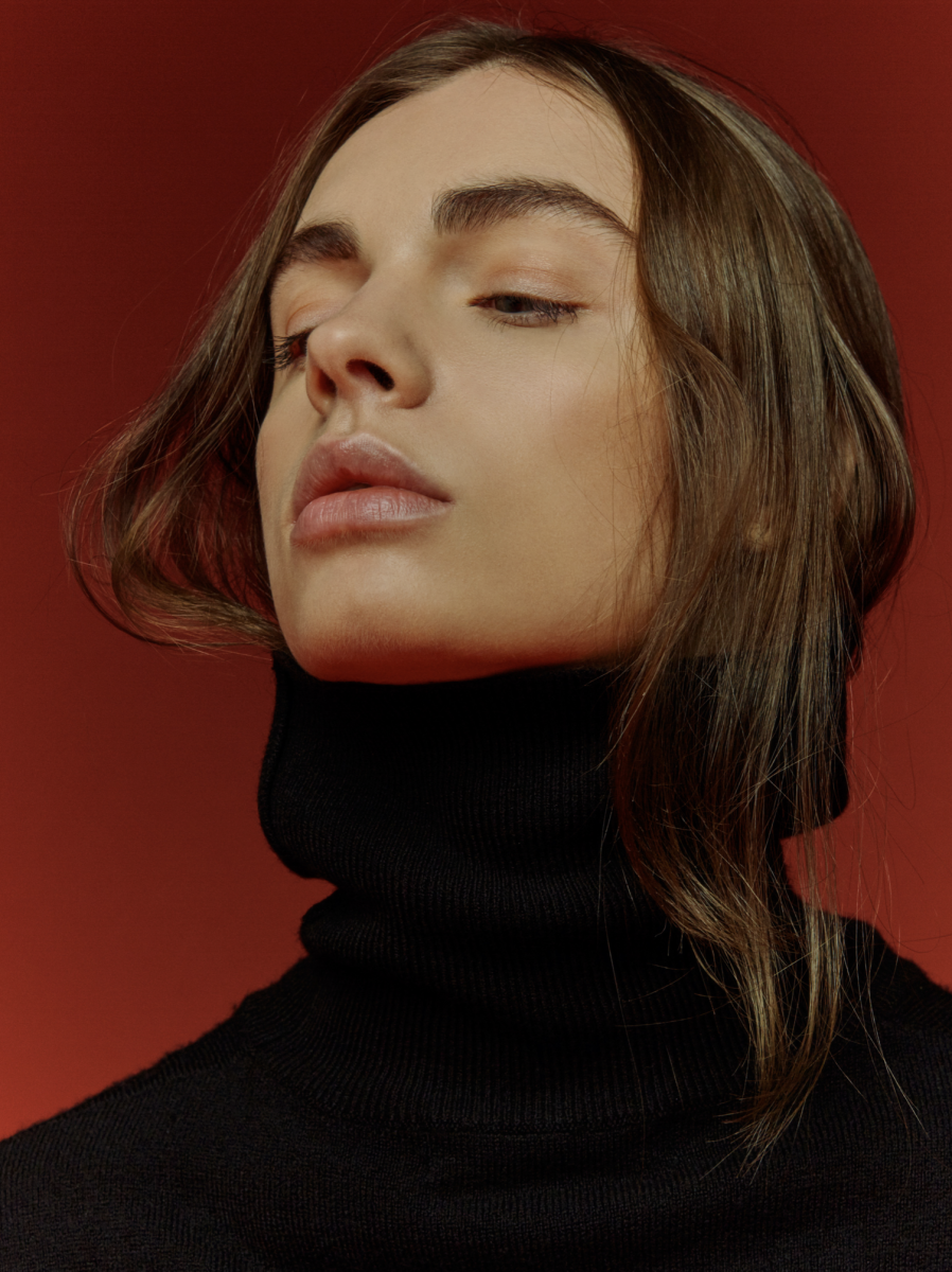 Balistarz-model-Tina-Veshaguri-portrait-headshot-with-a-red-background-and-a-turtleneck