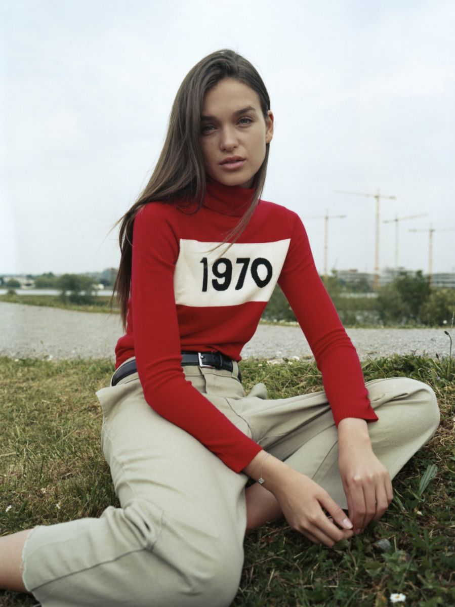 Balistarz-model-Valeria-Rudenko-portrait-sitting-on-grass-shoot-in-red-1970-turtleneck-clear-beautiful-water-in-the-background